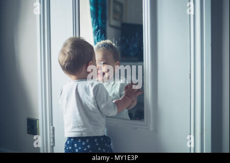 A cute little baby is playing with his own reflection - Stock Photo