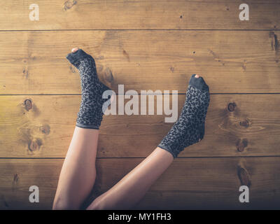 Overhead shot of a woman's feet in worn socks on the floor - Stock Photo