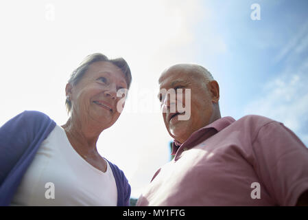Low angle portrait of a healthy elderly couple outside in summer sunshine looking very contented and happy with life - Stock Photo