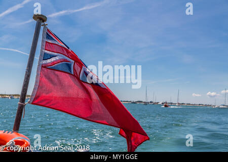 The red ensign flag as used in British maritime law signifies a civilian vessel, here,  cruising off the beach at West Wittering, Sussex, England, UK - Stock Photo