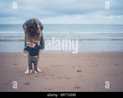 A young mother is helping her little baby walk on the beach - Stock Photo