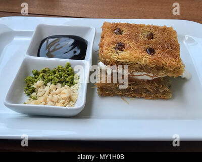 Turkish Dessert Kadayif with Ice Cream, Pistachio, Hazelnut Powder and Chocolate Sauce served at Restaurant / Knife. Traditional Food. - Stock Photo