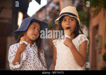 Two cute Asian sisters eating icecream together whilst on holiday in the Alsace region of France during summer - Stock Photo