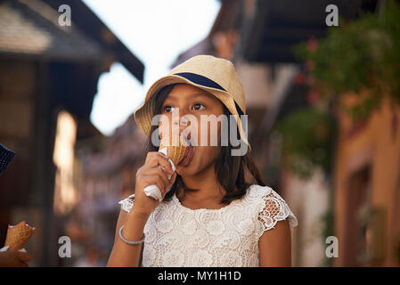 Little cute Asian girl wearing a straw hat eating icecream whilst on holiday in the Alsace region of France in summer sunshine on a hot day - Stock Photo