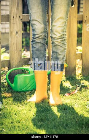 Gardener wearing yellow wellies boots in garden, toned image - Stock Photo