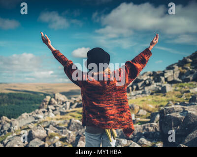 A young woman wearing a hat is raising her arms in the wilderness - Stock Photo
