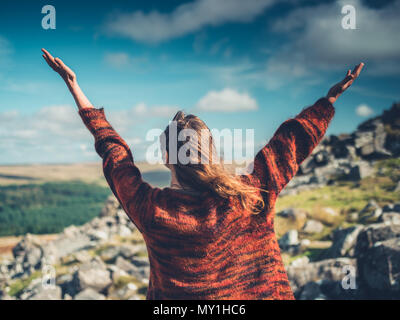 A young woman is raising her arms in the wilderness - Stock Photo