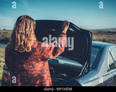 A young woman is opening the trunk of her car in the wilderness - Stock Photo