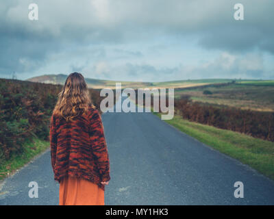 A young woman is standing in the road running through a moor - Stock Photo