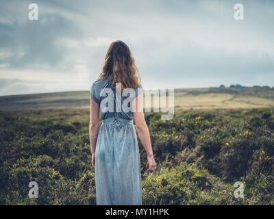 A beautiful young woman is wearing an elegant dress and is walking on the moor