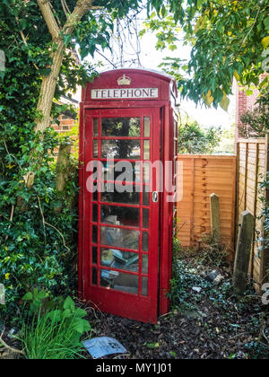 An old red telephone box used as a book swap location in a Wiltshire village. - Stock Photo
