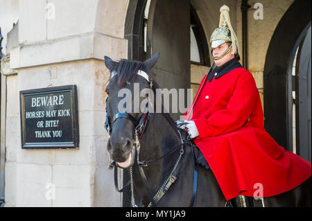 LONDON - OCTOBER 31, 2016: Mounted Queen's Life Guard of the Household Cavalry sits on his horse in an archway facing Whitehall. - Stock Photo