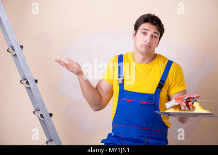 Young contractor employee applying plaster on wall - Stock Photo