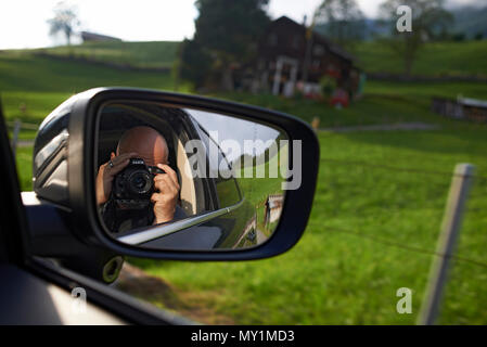 Close up of a photographer with a DSLR camera taking a photo of himself in the outside car mirror whilst sitting in the car on the way to the mountain - Stock Photo