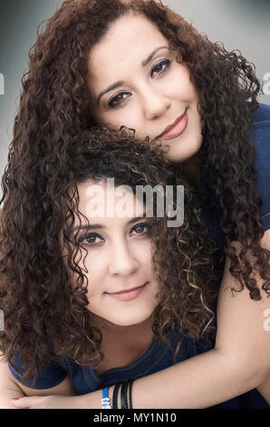 Twin sisters with curly hair hugging - Stock Photo