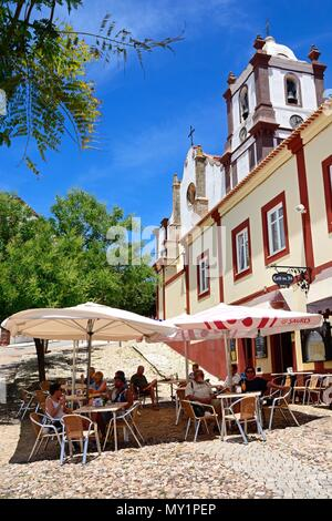 Tourists relaxing at a pavement cafe with the Gothic cathedral (Igreja da Misericordia) bell tower to the rear, Silves, Portugal, Europe. - Stock Photo