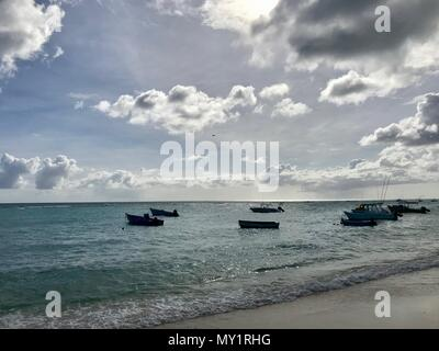 Scenic panoramic view of a beautiful sand beach in Barbados (Caribbean Island - West Indies) with a blue sky, white clouds & fishing boats on sea - Stock Photo
