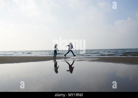 Two young sisters running and jumping across water along the beach with their reflections in the water - Stock Photo
