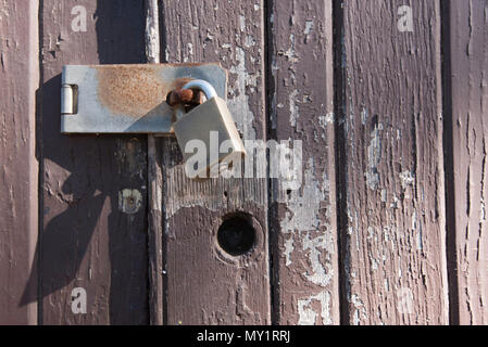 An old timber door with cracked and peeling paint secured by a brass padlock - Stock Photo