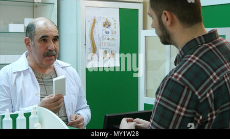 Senior pharmacist and young customer discussing medications - Stock Photo