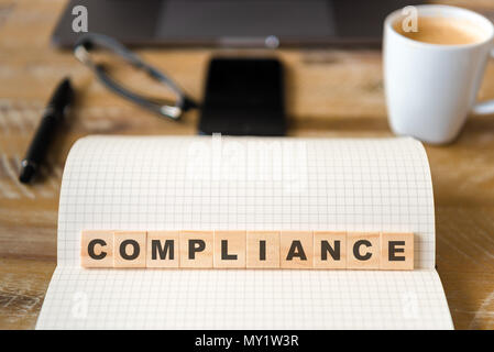 Closeup on notebook over wood table background, focus on wooden blocks with letters making Compliance text. - Stock Photo