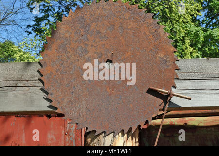 A huge rusty circular saw hanging on a rustic fence. Sunny spring day shot - Stock Photo