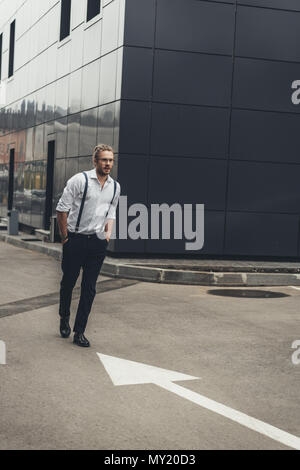 Handsome stylish young businessman in eyeglasses walking with hands in pockets outside modern building - Stock Photo