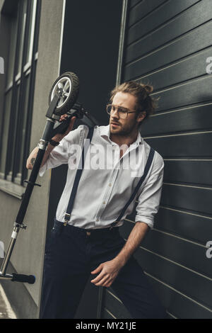 Stylish young man in spectacles and suspenders holding scooter while standing outside modern building - Stock Photo