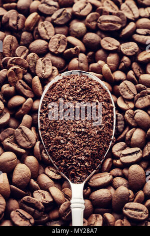 Ground coffee in a spoon on roasted coffee beans background. Top view. Concept of coffee grinding - Stock Photo