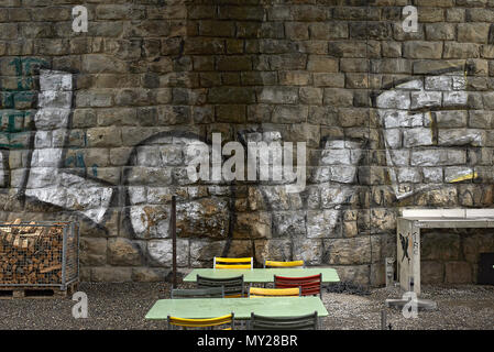 The word love written on a stone wall with a couple of empty tables and chairs in front of it - Stock Photo