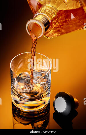 Whiskey pouring from a bottle to a whiskey glass with ice. Cap is on the table. Moody close up shoot. - Stock Photo