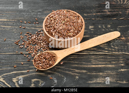 Flax seeds in a spoon and mixing bowl on wooden background - Stock Photo