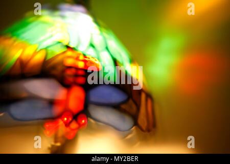 A brightly coloured and illuminated Tiffany style lamp - Stock Photo