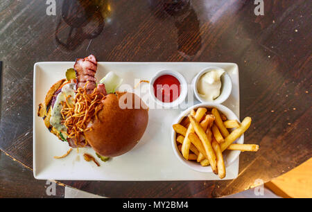 Typical British pub food: Cheeseburger in a bun with bacon and French fries (chips) with tomato ketchup and mayonnaise dips served on a white plate - Stock Photo