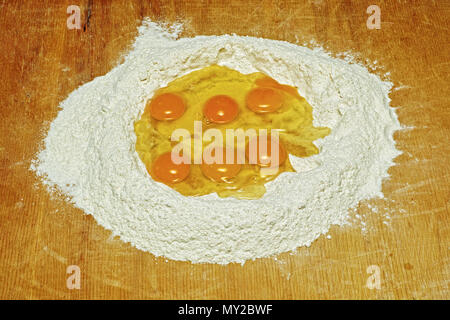 eggs and flour ready for the dough - Stock Photo