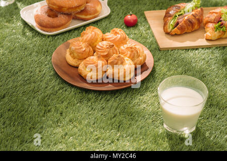 Healthy picnic for a summer vacation with freshly baked croissants, fresh fruit and fruit salad, sandwiches and a glass of refreshing orange juice lai - Stock Photo