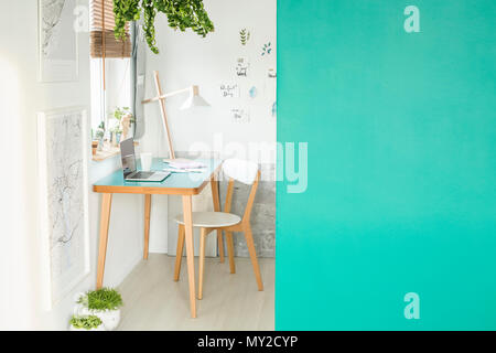 Green empty wall with place for your product in white open space interior with laptop on a wooden desk, fresh plants and handmade posters hanging on t - Stock Photo