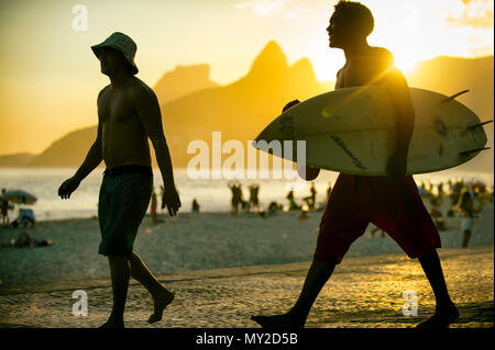 RIO DE JANEIRO - MARCH 20, 2017: Sunset silhouettes of two young surfers with surfboard at Arpoador, Ipanema with two brothers mountain in background - Stock Photo