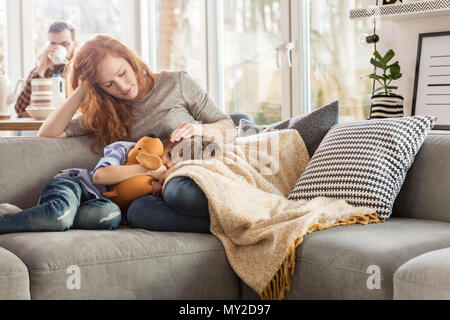 Mother taking care of her sleepy child while sitting on a couch in the living room - Stock Photo