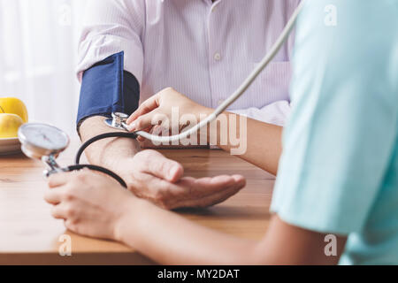 Closeup of patient's hand and a doctor measuring his blood pressure on a wooden desk - Stock Photo