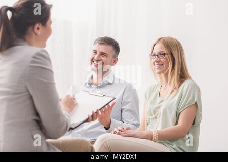 Psychotherapist analyzing a young, happy married couple in a bright office - Stock Photo
