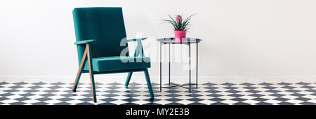 Green armchair and metal end table with fresh plant in pink pot standing in white room interior with place for your chair - Stock Photo