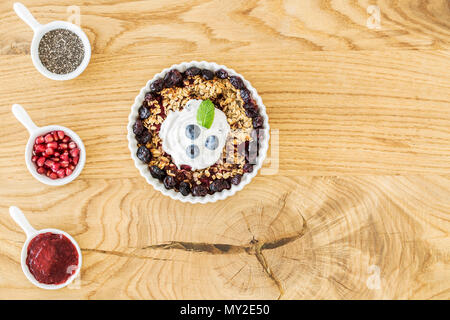Top view of breakfast granola with fruit, cups with pomegranate, jam and chia seeds and place for your ingredients on a wooden kitchen table - Stock Photo