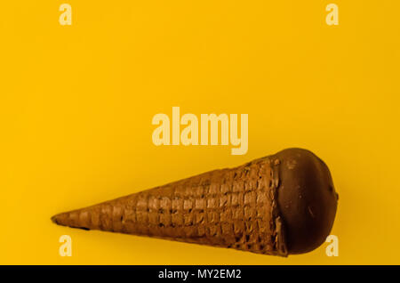 Vanilla ice cream with cranberry jam in a sugar cone dipped in chocolate on yellow background.Pastel colour.Cool off in the hot summer.Copy space top. - Stock Photo