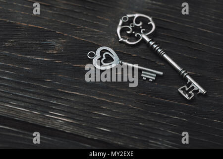 Two vintage bronze keys on a wooden table. Close-up view