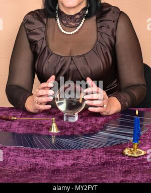 Female fortune teller looks in the future magic ball - Stock Photo