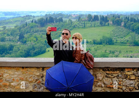 tourists taking selfie in san gimignano, tuscany, italy - Stock Photo