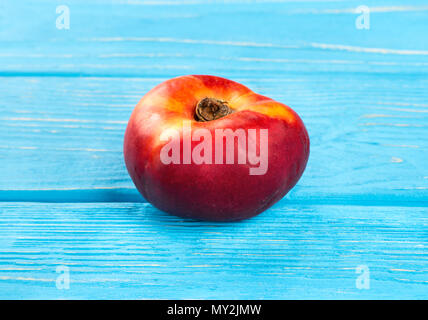 Fresh flat peach on a blue wooden background - Stock Photo