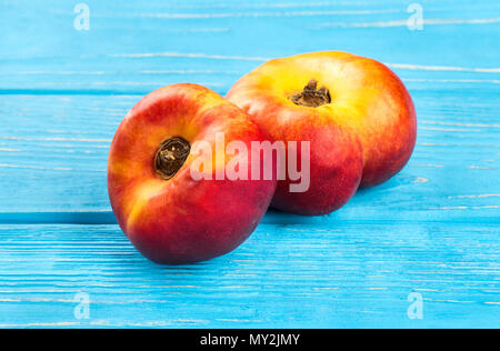 Two ripe flat peaches on blue table - Stock Photo