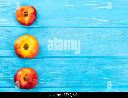 Three ripe flat peaches on a empty wooden background, top view - Stock Photo